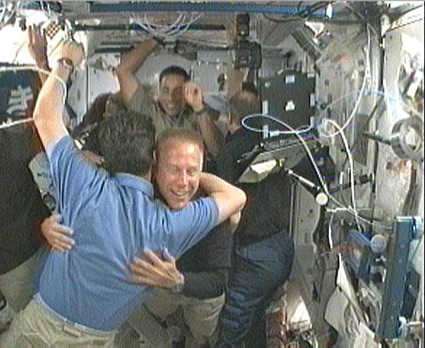The Expedition 20 and STS-127 crews greet each other after the hatches between the two vehicles were opened. Credit: NASA TV